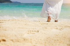 A beautiful carefree Woman relaxing at the beach enjoying her su. N dress freedom wear Stock Photography