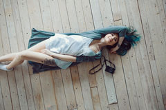 Beautiful carefree young casual woman lying on the wooden floor. Top view stock photo