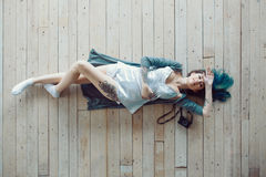 Beautiful carefree young casual woman lying on the wooden floor Royalty Free Stock Photo