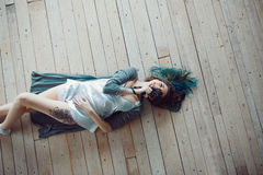 Beautiful carefree young casual woman lying on the wooden floor Royalty Free Stock Images