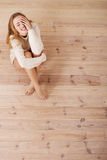 Beautiful carefree young casual woman sitting on the floor. Royalty Free Stock Photography