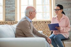 Beautiful caregiver providing help for senior man. Duties of caregiver. Appealing glad caregiver using clipboard while wearing glasses and talking to senior man royalty free stock images