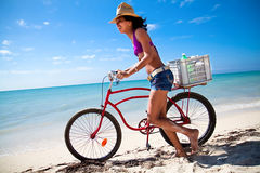 Beautiful caribbean woman with bicycle. Waking on a topical beach Stock Photography