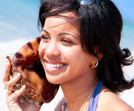 Beautiful caribbean woman holding a conch shell Royalty Free Stock Image
