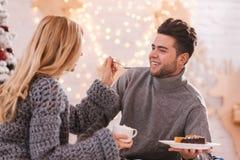 Beautiful caring woman feeding her boyfriend Stock Photos