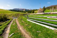 Beautiful Carpathian countryside in springtime. Dirt road down the hill and haystack behind the wooden fence. mountain ridge with snowy tops in the distance Stock Images
