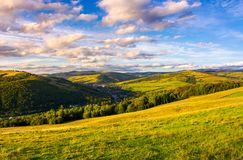 Beautiful Carpathian countryside at sunset. Village down in the valley in shade of a nearby mountain. beautiful colorful sky with clouds. Great water dividing Royalty Free Stock Photo