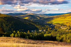 Beautiful Carpathian countryside at sunset. Village down in the valley in shade of a nearby mountain. beautiful colorful sky with clouds. Great water dividing Royalty Free Stock Photography