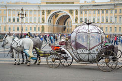 Beautiful carriage on Palace Square. People in carriage at Palace Square near Winter Palace of St. Petersburg. Summer 2016. Royalty Free Stock Images