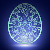 Beautiful carved butterfly on eggshell  on blue background. And with white glow Stock Photo