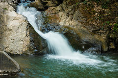 Beautiful cascade through mountain rocks Stock Photography