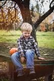 Beautiful casual blond child sitting outdoor on table and laughing. Autumn Stock Images