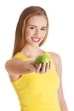 Beautiful casual caucasian woman holding fresh green apple. Isolated on white Stock Photography