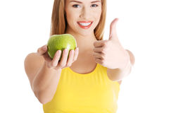 Beautiful casual caucasian woman holding fresh green apple. Royalty Free Stock Image