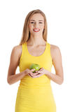 Beautiful casual caucasian woman holding fresh green apple. Stock Photo