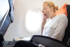 Beautiful Casual Caucasian Woman Yawning On Airplane Flight While Reading In Flight Magazine. Royalty Free Stock Photos