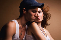 Beautiful casual couple in jeans. Portrait of a beautiful casual couple in jeans sitting together over wooden background. studio shot Royalty Free Stock Image