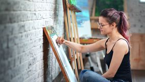 Beautiful casual female illustrator painting sketch using gray pencil at art workshop studio. Medium shot. Happy enthusiastic woman enjoying drawing picture stock footage