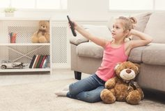 Beautiful casual little girl watching tv. Little casual girl watching tv at home. Female kid sitting on floor carpet with her toy friend teddy bear, holding Royalty Free Stock Photo