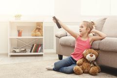 Beautiful casual little girl watching tv while sitting on the floor at home. Little casual girl watching tv at home. Female kid sitting on the floor carpet with Stock Photo