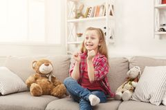 Beautiful casual little girl watching tv while sitting on sofa at home. Happy little casual girl watching tv at home. Excited female kid sitting on sofa with her Stock Images
