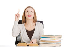 Beautiful casual student woman sitting by stack of books and poi Stock Image