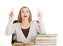 Beautiful casual student woman sitting by stack of books and poi Stock Photo