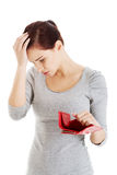 Beautiful casual woman with empty wallet, worrying. Royalty Free Stock Images