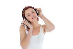 Beautiful casual woman enjoying music through headphones Royalty Free Stock Images