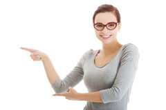 Beautiful casual woman in eyeglasses pointing aside. Stock Image