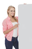 Beautiful casual woman holding and pointing at blank white board Stock Photos