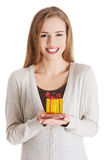 Beautiful casual woman holding small present in hands. Royalty Free Stock Image