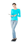 Beautiful casual woman holding a tablet. Isolated on white Stock Photo