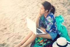 Beautiful casual woman with a laptop on the beach royalty free stock photography