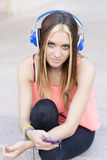 Beautiful casual woman listening to music with headphones and ph Stock Image