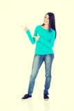 Beautiful casual woman pointing on copy space. Royalty Free Stock Image