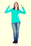 Beautiful casual woman pointing on copy space. Royalty Free Stock Photos