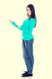Beautiful casual woman pointing on copy space. Royalty Free Stock Images