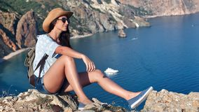 Beautiful casual woman relaxing sitting on top of high mountain over sea harbour. Full shot. Backpacker hipster female in hat sunglasses admiring amazing stock video