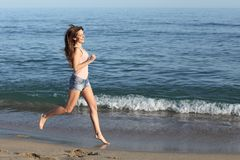 Beautiful casual woman running on the beach Royalty Free Stock Images