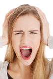 Beautiful casual woman screams and covers her ears. Royalty Free Stock Image