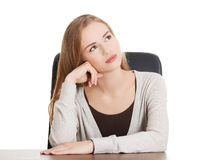 Beautiful casual woman sitting by a desk and day- dreaming. Royalty Free Stock Image