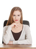 Beautiful casual woman sitting by a desk. Isolated on white Stock Image