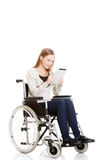 Beautiful casual woman sitting on w wheelchair with tablet. Royalty Free Stock Photo