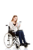 Beautiful casual woman sitting on w wheelchair with tablet. Royalty Free Stock Images