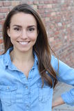 Beautiful casual woman smiling -  over a brick wall background Royalty Free Stock Images