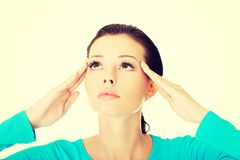Beautiful casual woman touching her temples. Royalty Free Stock Images