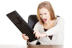 Beautiful casual woman trying to destroy keyboard. Royalty Free Stock Photos