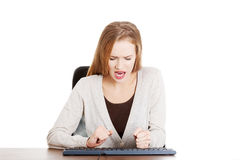 Beautiful casual woman writing on keyboard with anger. Stock Image