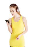 Beautiful casual woman in yellow top is listening to music. Isolated on white Royalty Free Stock Photography